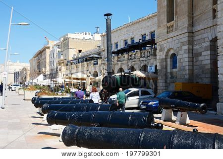 VITTORIOSA, MALTA - MARCH 31, 2017 - Row of Cannons along the waterfront with pavement cafes to the rear Vittoriosa (Birgu) Malta Europe, March 31, 2017.