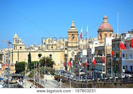 VITTORIOSA, MALTA - MARCH 31, 2017 - Elevated view along the waterfront buildings towards St Lawrence church Vittoriosa (Birgu) Malta Europe, March 31, 2017.