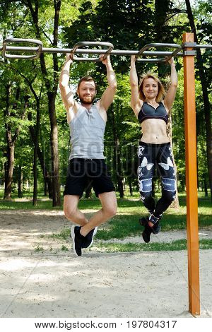 Young sportive couple doing pull-ups exercises on crossbar in a park at summer day.