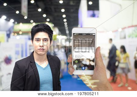 iot internet of things translation technology concept foreigner use smart phone translate meaning how to go to the center hall in English to Chinese language by voice command while loss in the hall