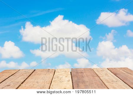 perspective old wooden board empty table in front of blur background of bright cloudy sky can be used for display or montage your products. Mock up for displaying product.