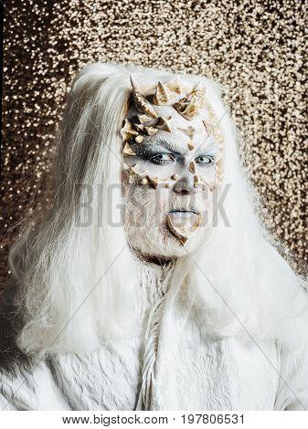 Demon In White Cloth On Golden Bokeh Background