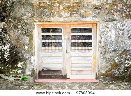 A view of closed wooden doors surrounded by a stone wall