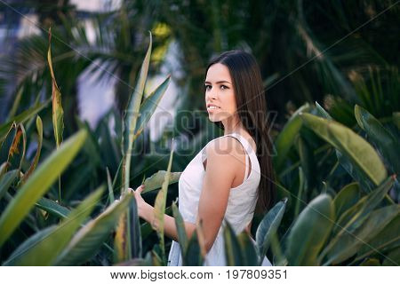 An elegant lady on a natural green tropical forest background. A beautiful female in a white dress walking through the summer park. A serious and cute brunette girl on natural background.