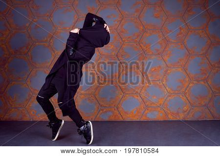 Young dancer standing on his tiptoes near the wall. Urban style