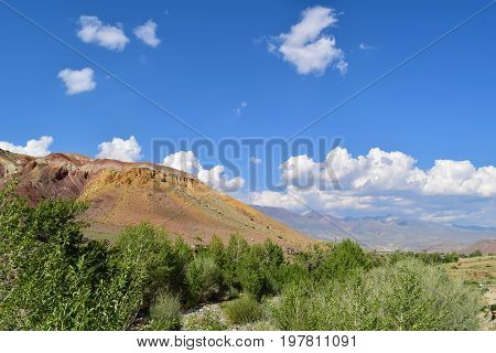 Slope of red hill in Altai mountains. Background of blue sky and white clouds. Altay Republic Siberia Russia.