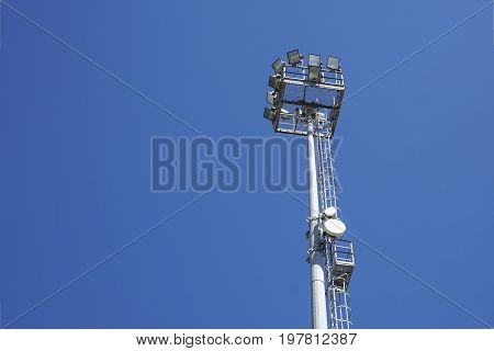 Outdoor stadium lights and telecommunication tower against daytime blue sky. Single row of bulbs with cell phone gsm antennas on tall metal pole. Room for text, copy space. Blue sky, wispy clouds.
