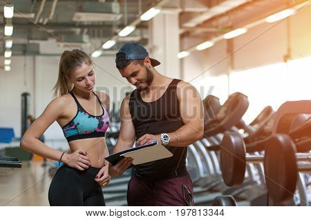 Young blonde woman and her personal trainer discussing training plan in gym. Male coach and female client working out in modern fitness center. Healthy lifestyle, fitness and sports concept.