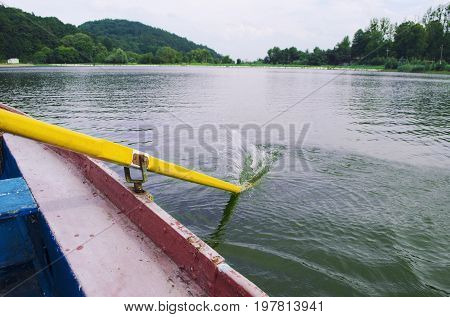 Yellow paddle in the water. Boating on river. Oar of boat touching water.