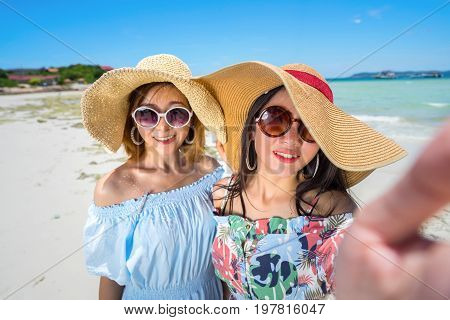 Young woman asian buddy in hawaii dress with hat selfie camera view on sea beach summer fun and happy relax in vacation time