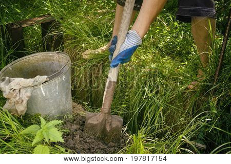 A manual worker digging a ditch with a shovel outdoor cropped photo
