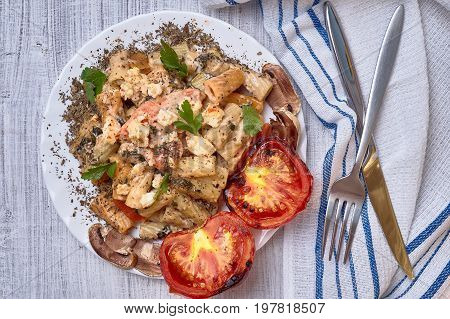 Paste from macaroni with vegetables, with tomatoes and seasoned with a basil. It is decorated with parsley. On a light background with ordinary devices.