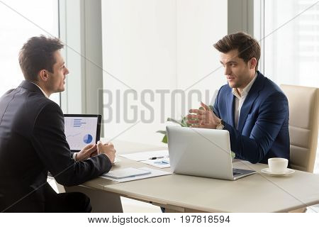 Serious businessmen in office discussing project ideas with laptops, executive business team creating plan, analyzing market and studying graphs charts, finding solutions for business improvement