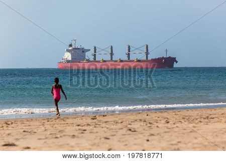 Ocean ship enters port closeby beach with young unidentified girl swimming