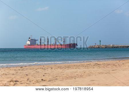 Ocean ship enters port between two pier beacons