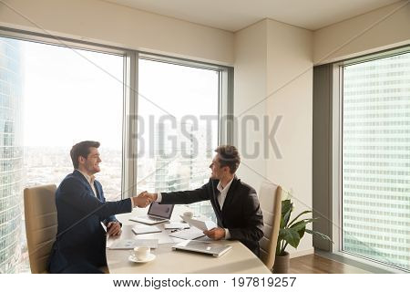 Two smiling businessmen shaking hands after successful negotiations sitting at office desk, big windows at background, happy business partners making agreement and handshaking, satisfied with result