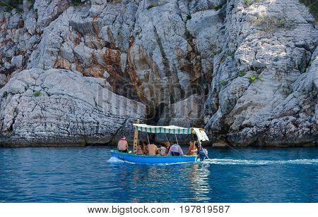 BUDVA RIVIERA MONTENEGRO - SEPTEMBER 19 2015: Unknown tourists swim by boat along picturesque rocky coast Budva Riviera Montenegro