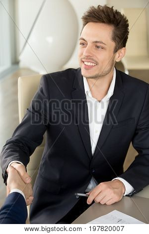 Young smiling businessman wearing black suit shaking male hand at meeting, nice to meet you at job interview, joining team and first impression, collaborative partner ready to negotiate, making deal