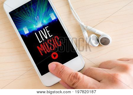Hand touch smart phone and ear phone with Live music word on wood table Internet marketing concept