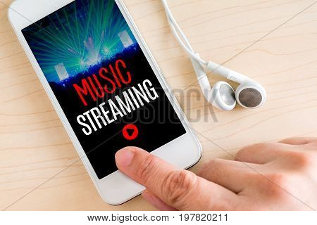 Hand touch smart phone and ear phone with Music Streaming word on wood table Internet marketing concept