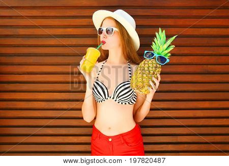 Woman With Funny Pineapple Drinks Juice Or Smoothies On Wooden Background
