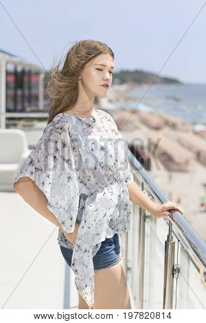 A beautiful girl in a light summer blouse and short denim shorts on the background of an expensive hotel near the sea. A cute girl stands sideways and her long fair-haired hair fluttering in the wind.