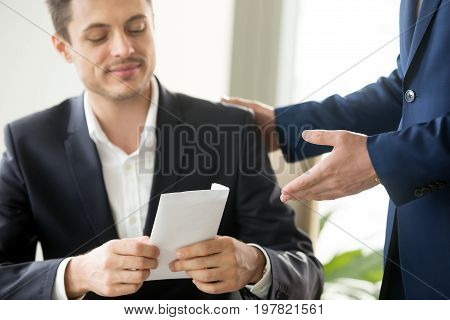 Happy corrupted businessman accepting bribe, male hand giving smiling office worker envelope salary at workplace, receiving business letter, bonus for good work, bribery and corruption concept poster
