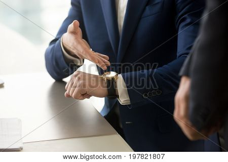 Close up view of businessman wearing suit pointing on hand expensive luxury wristwatch at meeting, showing unpunctual partner he is being late, punctuality management concept, time is money