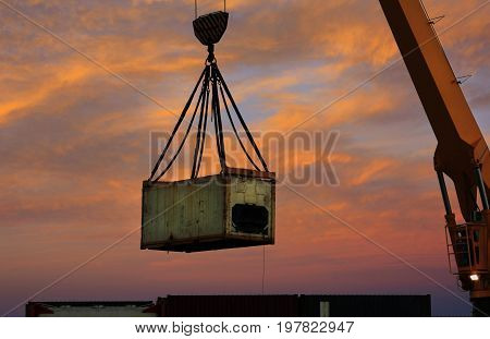 Containers being moved by a crane in the evening sunset