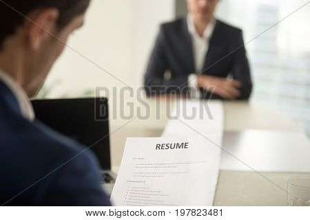 Perfect performance at job interview concept. Close up view over the shoulder at long sheet of paper with resume. Executive reading reviewing detailed cv, recruiter hr manager considering application
