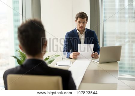 Surprised employer holding long sheet of paper, detailed resume of applicant at interview, astonished recruiter amazed with impressive career achievements, client submitting huge list of complaints