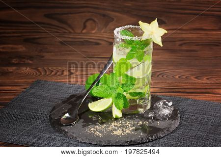 A glass of green alcohol mojito on a light brown wooden background. A cold mojito with liquor and rum on a black plate. Fresh mint leaves and yellow carambola. Drinks for summer parties. Copy space.