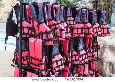 red pink life vest jackets hanging on rack outdoor for safety and protection while using in water such as swimming pool or out in the ocean or at sea