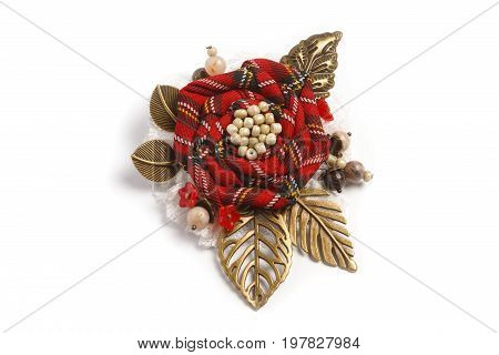 Handmade brooch in the form of a flower from a red checkered fabric with metal leaves