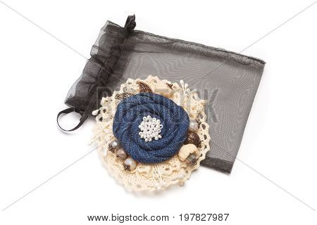 Handmade brooch having shape of the flower made from denim on white lace fabric