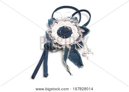 Simple pendant in the form of a handmade flower made of denim fabric on a white background