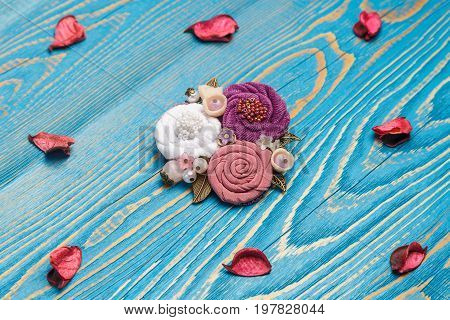 Brooch handmade consisting from of white pink and lilac flowers making from cloth on the blue background