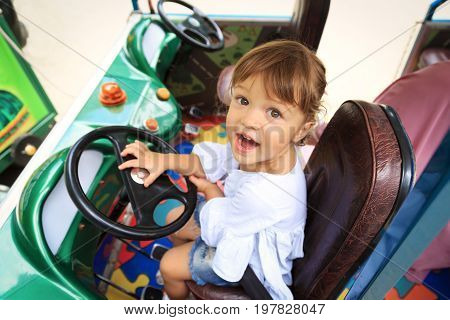 Little girl is happy sitting on the driver's seat of the children's car