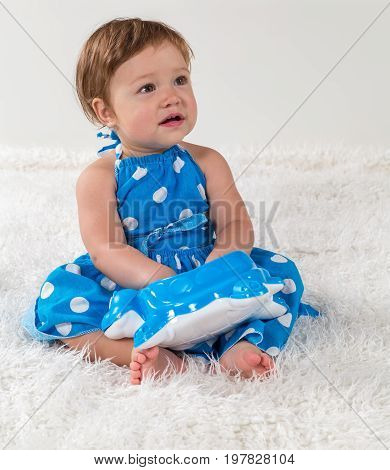 Little girl in a blue dress is sitting on the bed and looking to the side playing with a toy