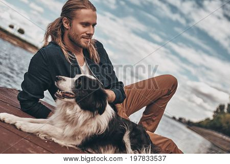 His best friend. Handsome young man and his dog sitting near the lake while spending time outdoors