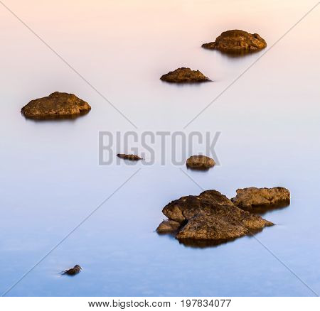 Abstract of rocks in quiet water taken during sunset in Cres