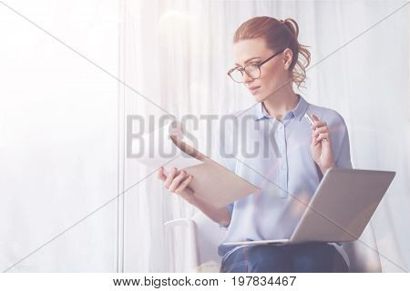 Distance work. Pleasant professional freelance worker holding notes and using laptop while sitting at home