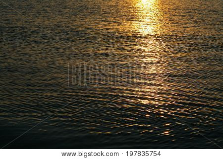 Background of the water surface at sunset is seen on a Baltic Sea in Kolobrzeg in Poland