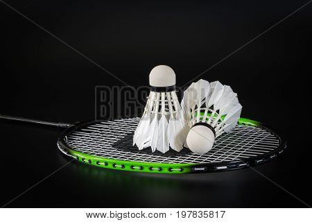 Badminton ball are placed on the net of badminton racket over black background. Sports and recreation concepts.