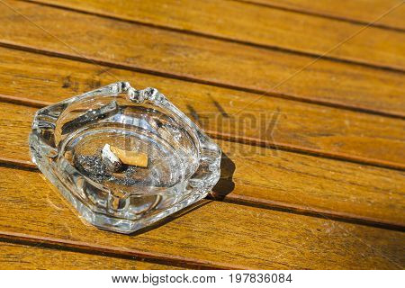 Cigarette butt with ash in the glass ashtray that is placed on a wooden table