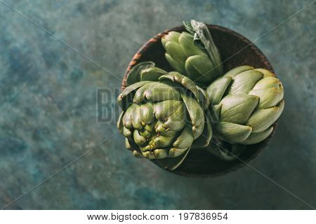 Ripe organic artichokes in a wooden bowl, background with copy space. Top view.