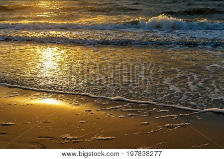 The rays of the sunset look at the gentle waves of the Baltic Sea which finally runs to the sandy beach of Kolobrzeg in Poland.