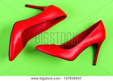 Pair Of Red Leather High Heel Shoes On Green Background