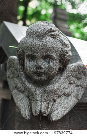 Antique statue of angel on tomb. Tombstone as a symbol of depression and sorrow in St. Petersburg. Necropolis of Alexander Nevsky Lavra. August 22 2017