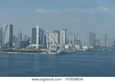 Panorama of Tokyo cityscape with modern skyscrapers bridge and docks on the waterfront.